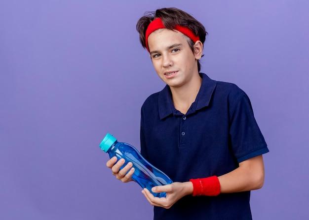 Lieto giovane bel ragazzo sportivo che indossa la fascia e braccialetti con bretelle dentali tenendo la bottiglia di acqua isolata sulla parete viola con spazio di copia
