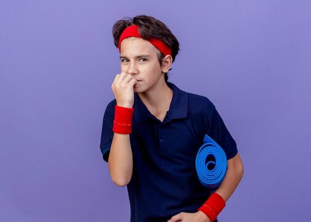 Soddisfatto giovane ragazzo sportivo bello che indossa la fascia e i braccialetti con le parentesi graffe dentali che tengono la stuoia di yoga che tocca le labbra isolate sulla parete viola con lo spazio della copia