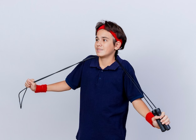 Pleased young handsome sporty boy wearing headband and wristbands with dental braces and jump rope around neck grabbing jump rope looking at side isolated on white background