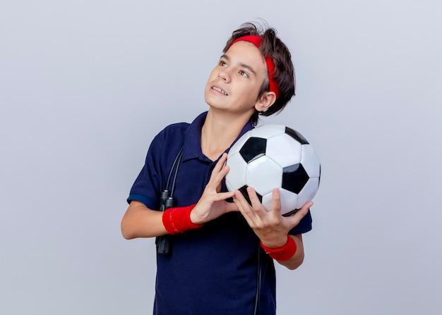 Felice giovane bel ragazzo sportivo che indossa la fascia e braccialetti con bretelle dentali e corda per saltare intorno al collo tenendo il pallone da calcio guardando in alto isolato su sfondo bianco con spazio di copia