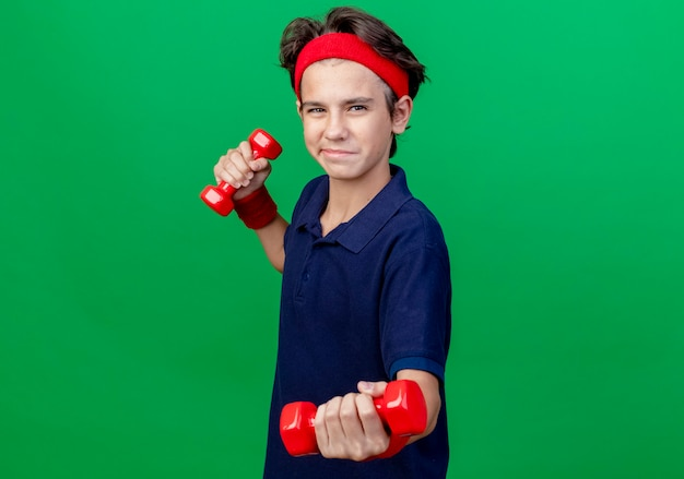 Pleased young handsome sporty boy wearing headband and wristbands with dental braces standing in profile view holding and stretching out dumbbells isolated on green background with copy space