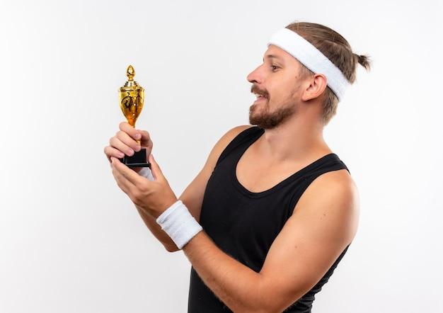 Довольный молодой красивый спортивный мужчина с головной повязкой и браслетами, держащий и смотрящий на кубок победителя, изолированный на белом пространстве