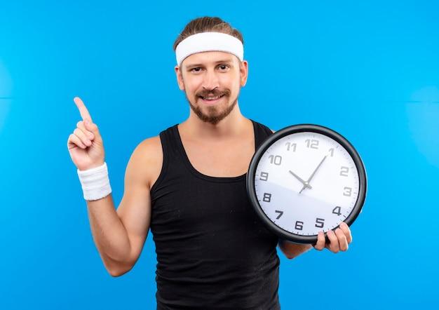Довольный молодой красивый спортивный мужчина с повязкой на голову и браслетами держит часы и указывает вверх изолирован на синем пространстве