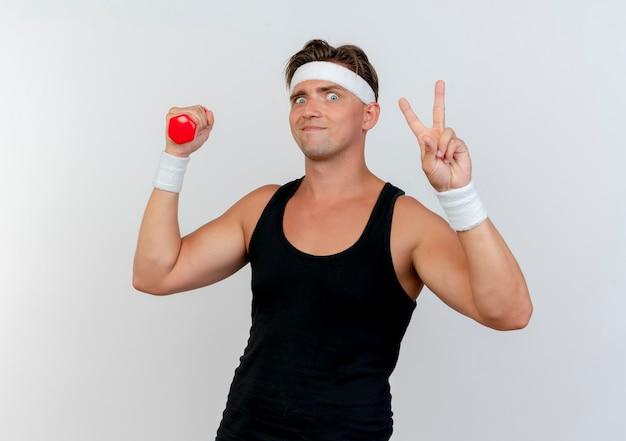 Довольный молодой красивый спортивный мужчина с головной повязкой и браслетами, держащий гантели и делающий знак мира, изолированный на белой стене