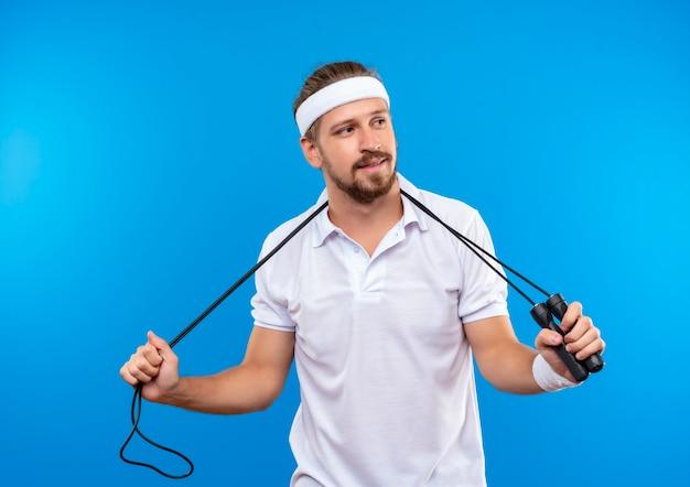 파란색 공간에 고립 된 측면을보고 그의 목에 줄넘기를 들고 머리띠와 팔찌를 착용하는 기쁘게 젊은 잘 생긴 스포티 한 남자