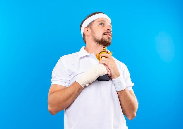 Довольный молодой красивый спортивный мужчина с повязкой на голову и браслетами держит кубок победителя и смотрит вверх с травмированным запястьем, перевязанным повязкой, изолированным на синем пространстве