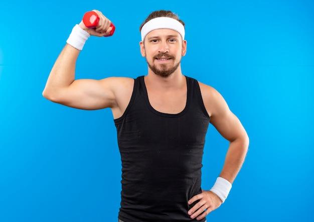 Довольный молодой красивый спортивный мужчина с головной повязкой и браслетами поднимает гантели и кладет руку на талию, изолированную на синем пространстве