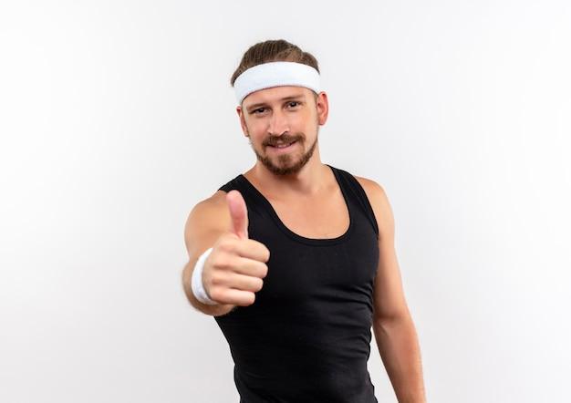 Довольный молодой красивый спортивный мужчина с головной повязкой и браслетами показывает большой палец вверх изолирован на белом пространстве