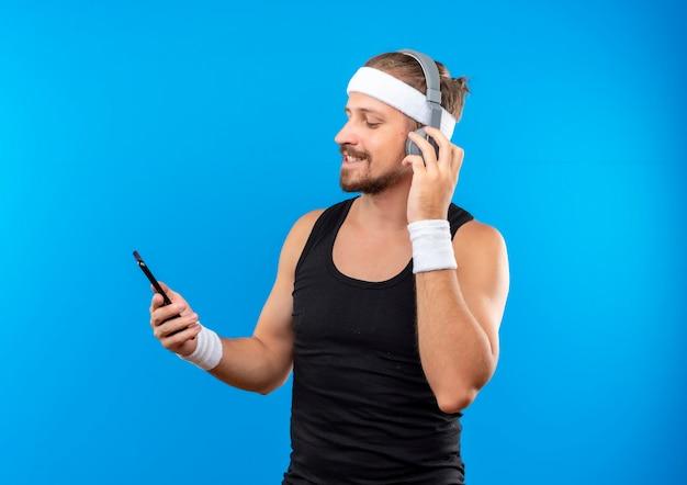 Довольный молодой красивый спортивный мужчина в головной повязке и браслетах с наушниками, держащий и смотрящий на мобильный телефон с одной рукой на наушниках, изолированном на синем пространстве