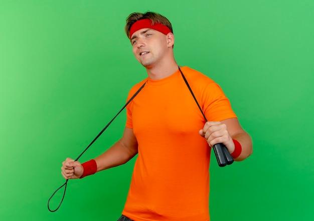 Довольный молодой красивый спортивный мужчина, носящий повязку на голову и браслеты со скакалкой на шее, держит скакалку, глядя прямо, изолированную на зеленой стене