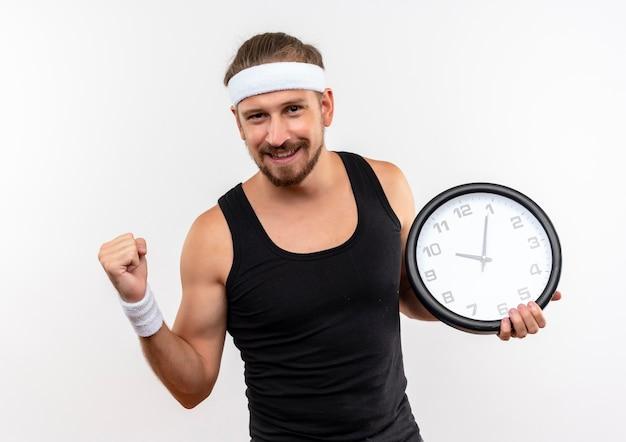 Soddisfatto giovane uomo sportivo bello che indossa la fascia e braccialetti che tengono l'orologio che stringe il pugno isolato su uno spazio bianco
