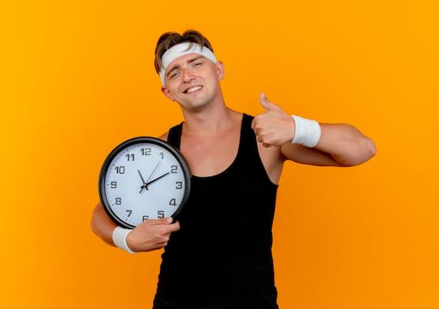 Soddisfatto giovane uomo sportivo bello che indossa la fascia e braccialetti che tengono l'orologio e che mostra il pollice in su isolato sulla parete arancione