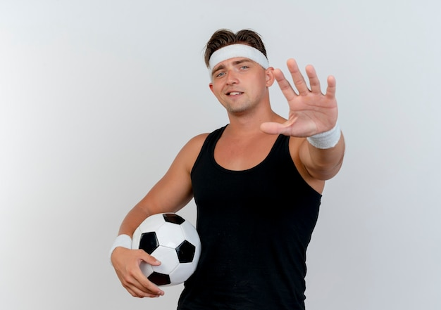 Pleased young handsome sporty man wearing headband and wristbands holding soccer ball and stretching out hand towards front isolated on white wall
