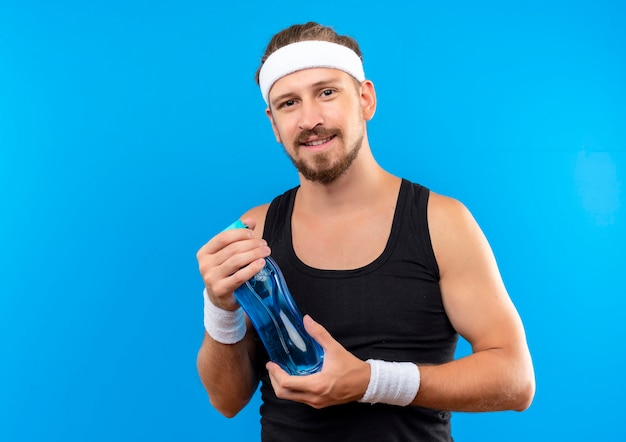 Soddisfatto giovane uomo sportivo bello che indossa la fascia e braccialetti che tengono la bottiglia di acqua che sembra isolato sullo spazio blu