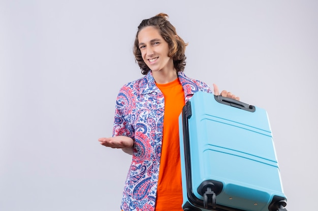 Довольный молодой красивый путешественник, держащий чемодан, указывая рукой на камеру, дружелюбно улыбаясь, стоя на белом фоне