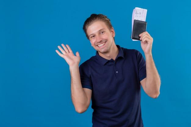 Довольный молодой красивый путешественник мужчина держит авиабилеты, весело улыбаясь, глядя в камеру, машет рукой, стоя на синем фоне
