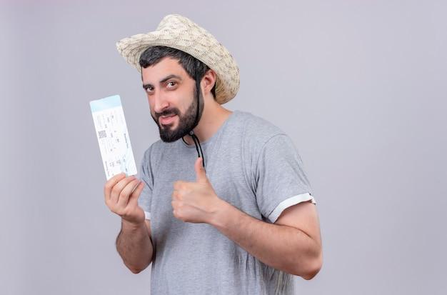 帽子をかぶって、白い壁に隔離された飛行機のチケットと親指を見せて喜んで若いハンサムな旅行者の男