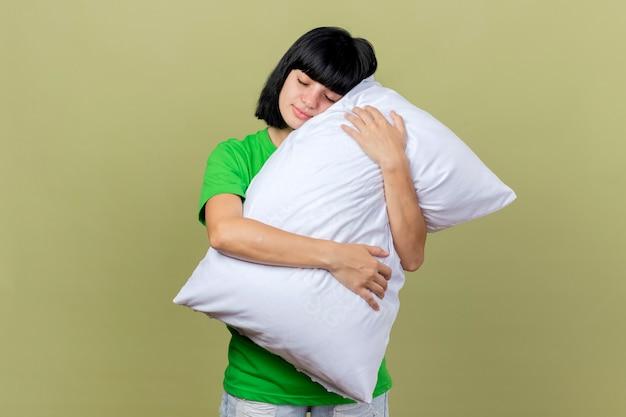 Felice giovane ragazza caucasica malata abbracciando cuscino mettendo la testa su di esso con gli occhi chiusi isolati su sfondo verde oliva con lo spazio della copia