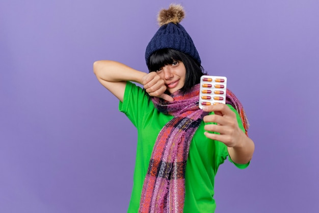 冬の帽子とスカーフを身に着けている若い病気の白人の女の子を喜ばせるカプセルのパックを伸ばして、コピースペースで紫色の背景に分離されたカメラを見て親指を上に表示