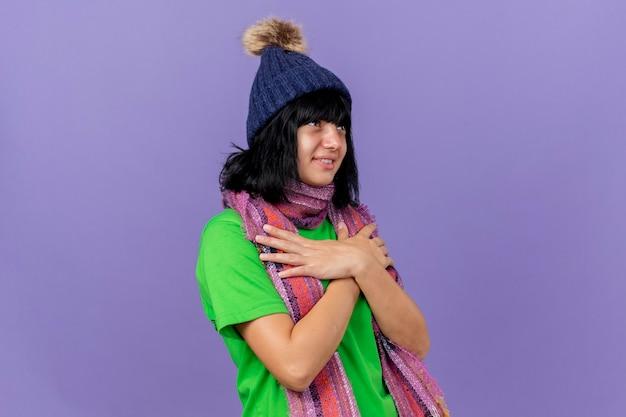 Felice giovane ragazza caucasica malata che indossa cappello invernale e sciarpa che osserva in su tenendo le mani incrociate sul petto isolato sulla parete viola con lo spazio della copia