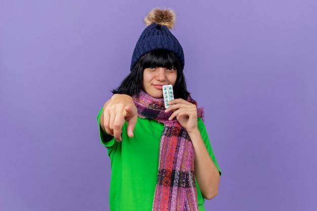 Lieta giovane ragazza caucasica malata che indossa un cappello invernale e sciarpa toccando le labbra con il pacchetto di capsule guardando e indicando la fotocamera isolata su sfondo viola con spazio di copia