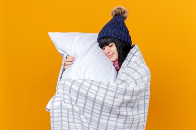 Lieta giovane ragazza caucasica malata indossando cappello invernale e sciarpa avvolta in plaid tenendo il cuscino toccando il viso con gli occhi chiusi isolato su sfondo arancione con spazio di copia