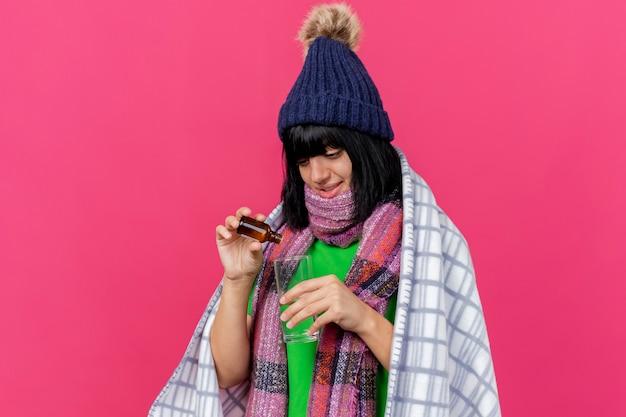 Lieta giovane ragazza caucasica malata indossando cappello invernale e sciarpa avvolto in plaid versando medicamento in vetro in un bicchiere d'acqua isolato su sfondo cremisi con spazio di copia