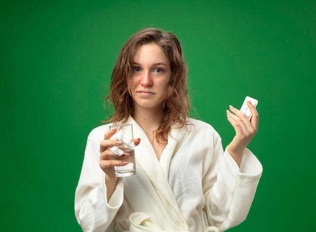 緑で隔離の丸薬と水のガラスを保持している白いローブを着てまっすぐ前を見て喜んで若い病気の女の子