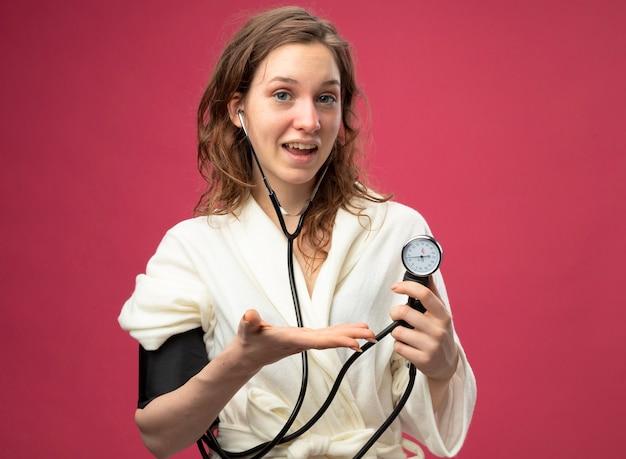 Довольная молодая больная девушка в белом халате, смотрящая прямо перед собой, измеряет собственное давление с помощью сфигмоманометра, изолированного на розовом