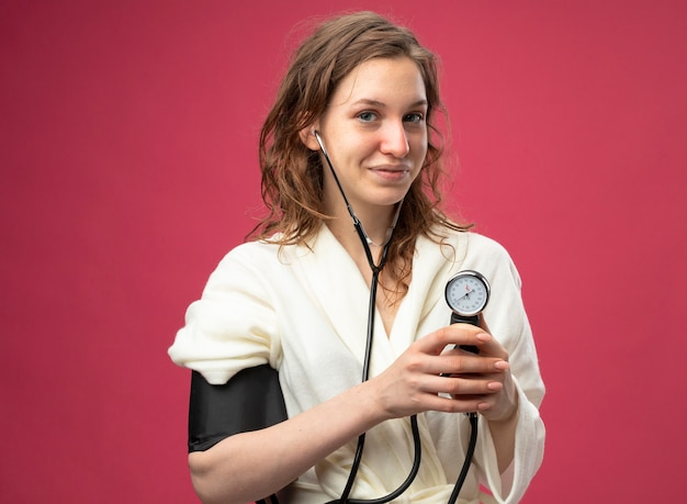Довольная молодая больная девушка в белом халате измеряет собственное давление с помощью сфигмоманометра, изолированного на розовом
