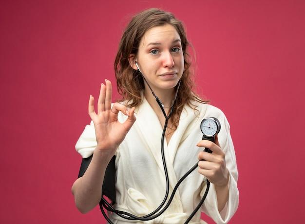 Довольная молодая больная девушка в белом халате измеряет собственное давление с помощью сфигмоманометра, показывая нормальный жест, изолированный на розовом