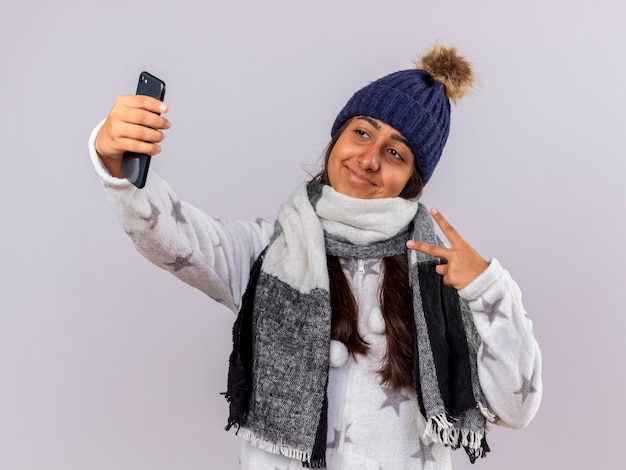Pleased young ill girl wearing winter hat with scarf take a selsie and showing peace gesture isolated on white background