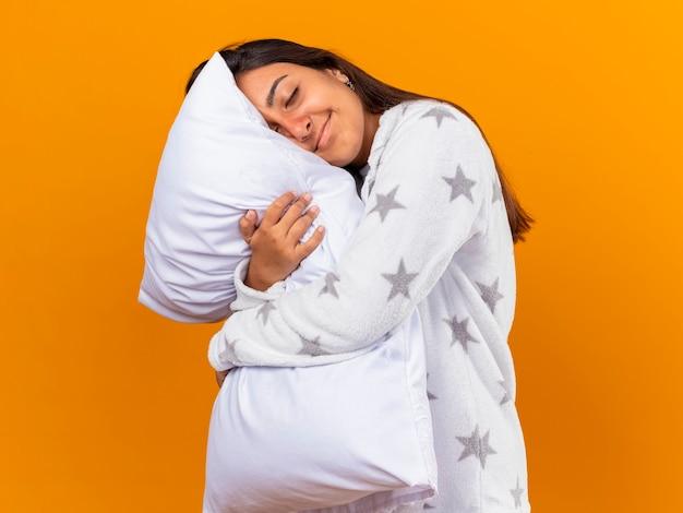黄色で隔離の枕を抱き締めて目を閉じて喜んで若い病気の女の子