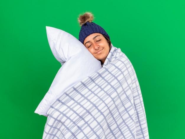 Довольная молодая больная девушка с закрытыми глазами в зимней шапке с шарфом, завернутым в клетчатую подушку для объятий, изолированную на зеленом фоне Бесплатные Фотографии