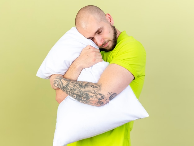 Pleased young ill man hugs pillow isolated on olive green wall