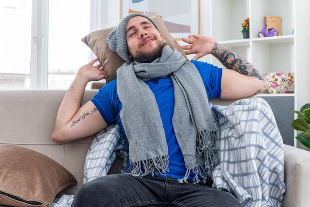 머리 뒤에 베개를 들고 거실 소파에 앉아 스카프와 겨울 모자를 쓴 젊은 아픈 남자가 눈을 감고 머리를 쉬고 있다
