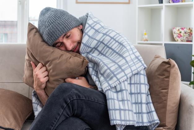 스카프와 겨울 모자를 쓴 젊은 아픈 남자가 거실에 있는 소파에 앉아 담요에 싸인 베개를 껴안고 눈을 감고 머리를 얹고 있는 것을 기쁘게 생각합니다.