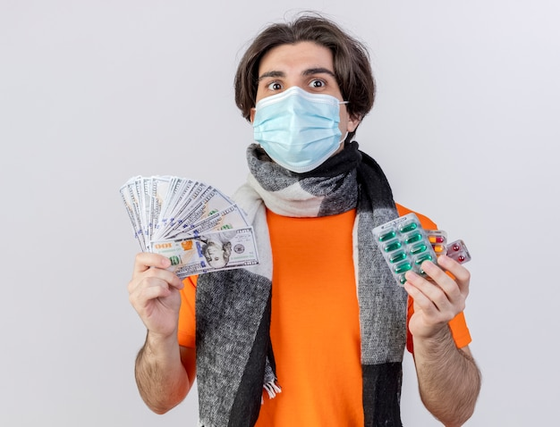 Pleased young ill man wearing scarf and medical mask holding money with pills isolated on white background