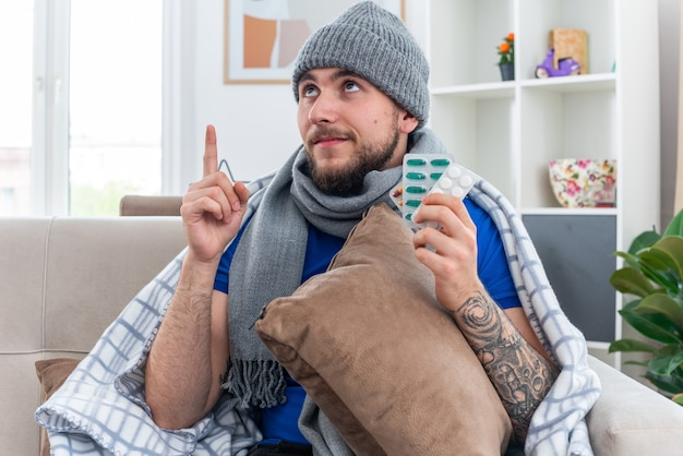 Felice giovane uomo malato che indossa una sciarpa e cappello invernale avvolto in una coperta seduto sul divano in soggiorno tenendo il cuscino tenendo le confezioni di pillole guardando e rivolto verso l'alto