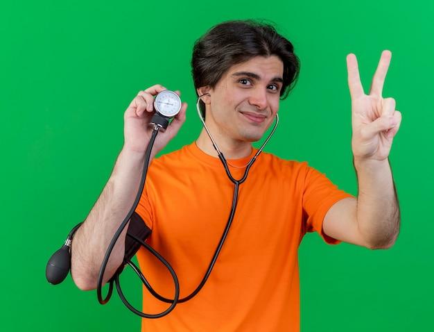 Довольный молодой больной человек со стетоскопом, держащий сфигмоманометр, показывающий жест мира, изолированный на зеленом