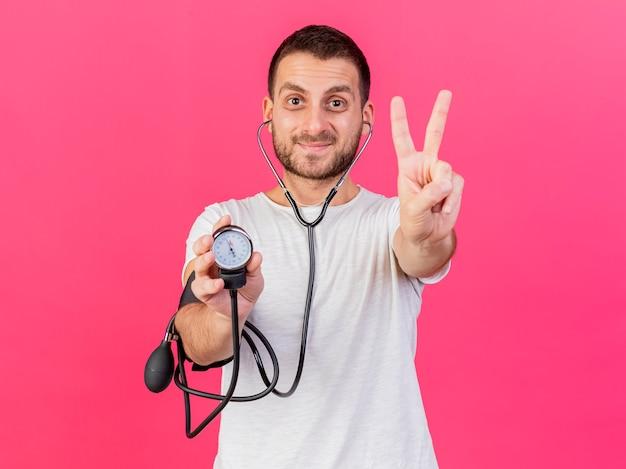 Довольный молодой больной человек со стетоскопом, держащий сфигмоманометр, показывающий жест мира на розовом фоне
