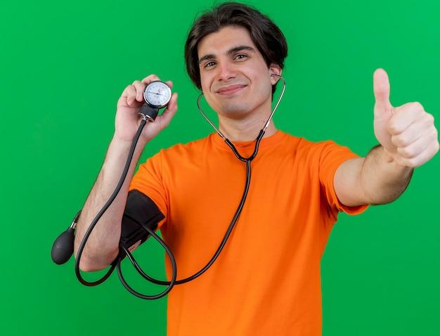 Felice giovane uomo malato che indossa uno stetoscopio tenendo lo sfigmomanometro che mostra il pollice in alto isolato sul verde
