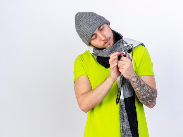 Felice giovane uomo malato che indossa cappello invernale e sciarpa tiene e guarda lo stetoscopio isolato sul muro bianco