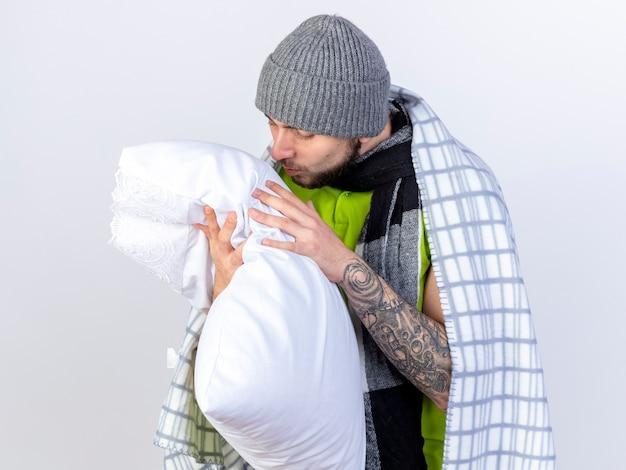 Felice giovane uomo malato che indossa un cappello invernale avvolto in plaid tiene e guarda il cuscino isolato sul muro bianco