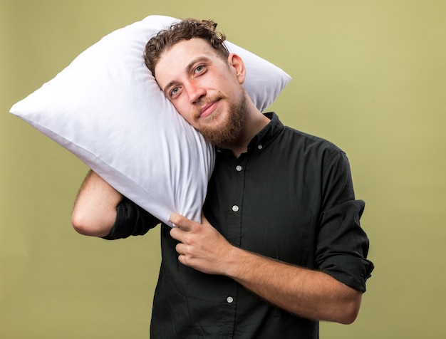 Pleased young ill slavic man holding pillow on shoulder isolated on olive green wall with copy space