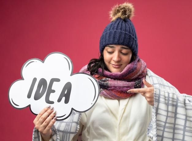 ピンクの壁に分離されたアイデアの泡を見て、指している格子縞の保持に包まれたローブの冬の帽子とスカーフを身に着けている若い病気の女性を喜ばせる