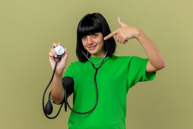 Довольная молодая больная женщина со стетоскопом показывает сфигмоманометр, указывающий на него, глядя на переднюю часть, изолированную на оливково-зеленой стене с копией пространства