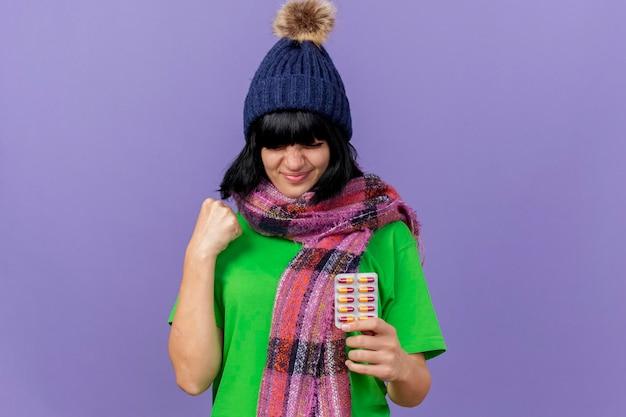 Felice giovane donna malata che indossa un cappello invernale e sciarpa che tiene il pacchetto di capsule facendo sì gesto isolato sulla parete viola con lo spazio della copia