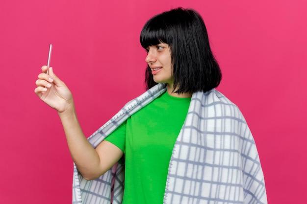 Довольная молодая больная женщина, завернутая в плед, держит и смотрит на термометр, изолированный на розовой стене