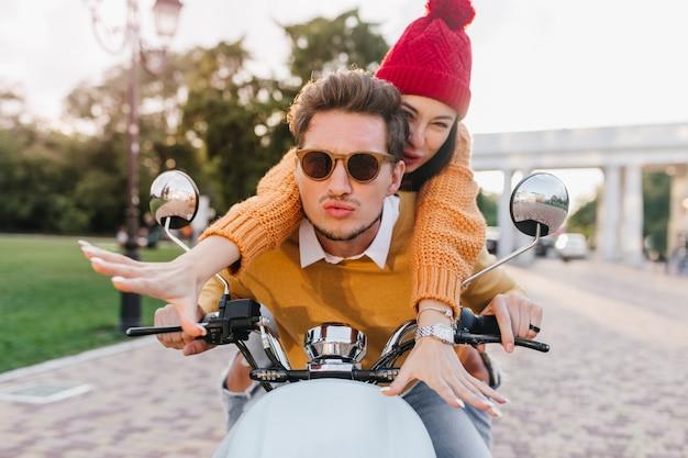 Довольная барышня в модных аксессуарах и вязаном свитере наслаждается быстрой поездкой с парнем